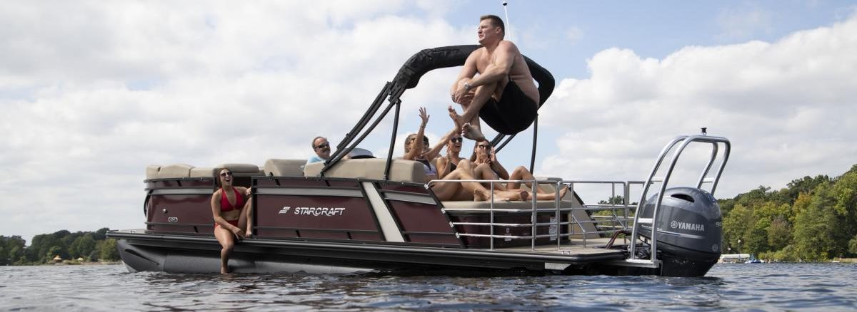 guy doing a cannonball off a starcraft pontoon